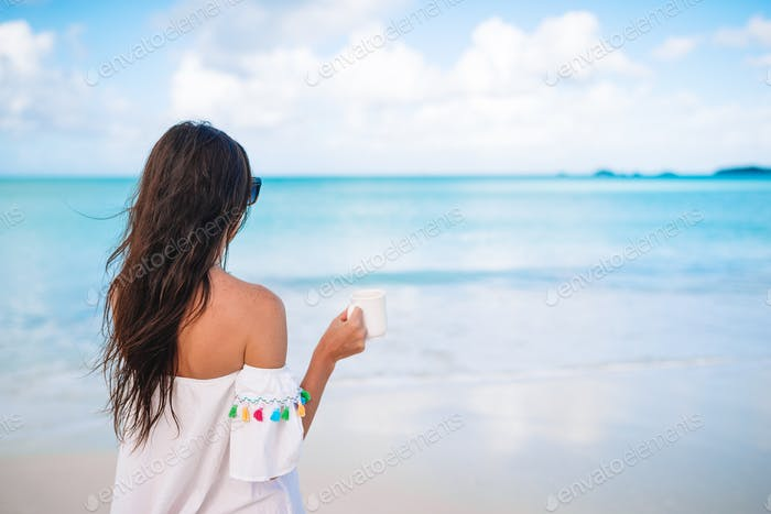 Young woman with cup of hot coffee enjoy holidays