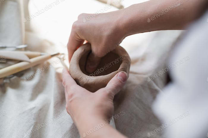 Female potter shaping piece of clay at the table. Woman making ceramic item. Pottery working