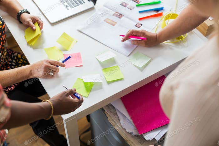 Coworkers writing on adhesive notes during meeting