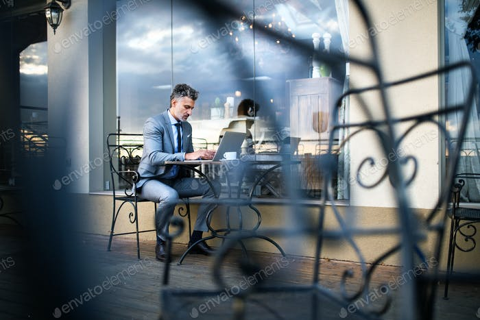 Mature businessman with laptop in an outdoor hotel cafe.