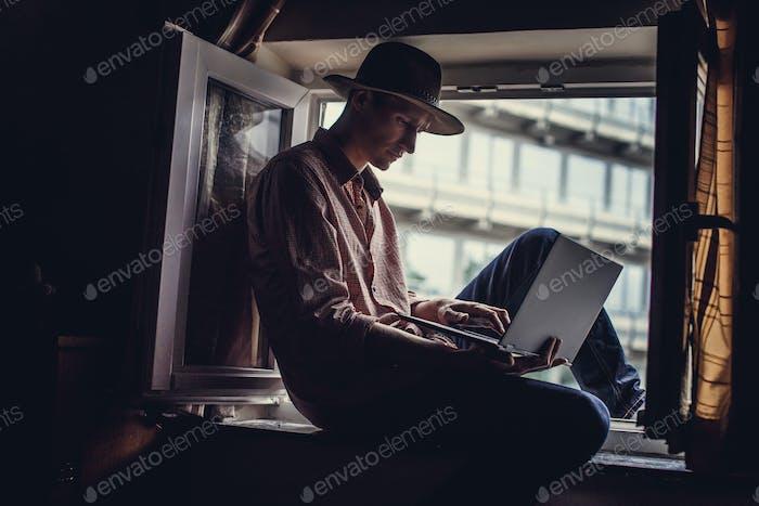 Guy in big hat sitting in the window
