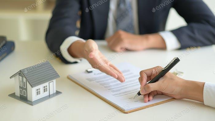 Unterzeichnung eines Kaufvertrags zwischen dem Hausmakler und dem Kunden.