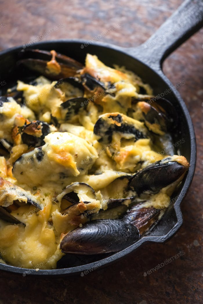 Frying pan with mussels under a cheese sauce on a brown background diagonal