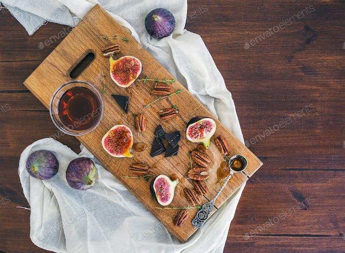 Frische Feigen, Schokolade und Pekanüsse mit Honig auf einem Holzschwein