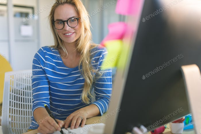 Female fashion designer looking and smiling at camera while drawing sketches at desk