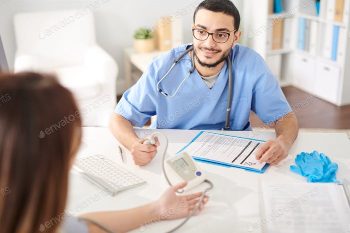 Middle-Eastern Doctor Working with Patient