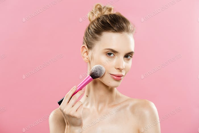 Beauty Concept - Closeup Beautiful caucasian woman applying makeup with Cosmetic Powder Brush