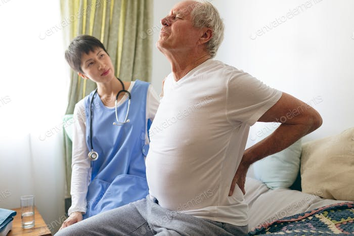 Male nurse helping senior male patient for back pain at retirement home