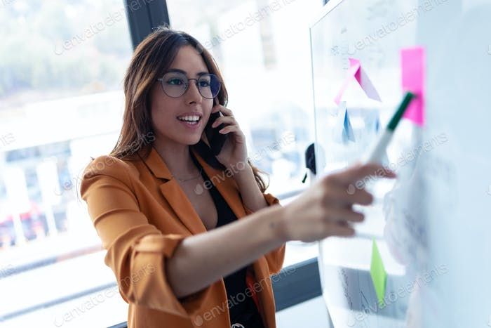 business young woman talking on mobile phone while working on white board with post it stickers