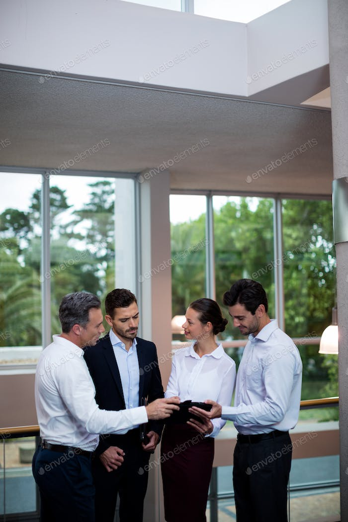 Business executives discussing over digital tablet
