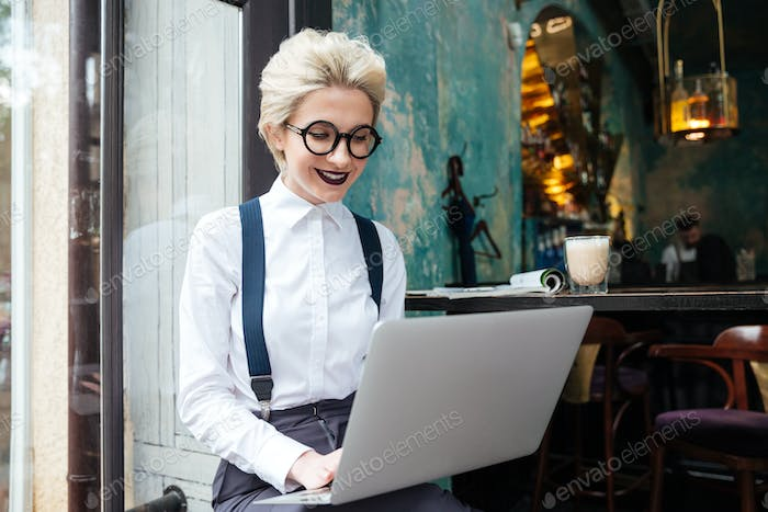 Beautiful young woman in glasses working on laptop and smiling