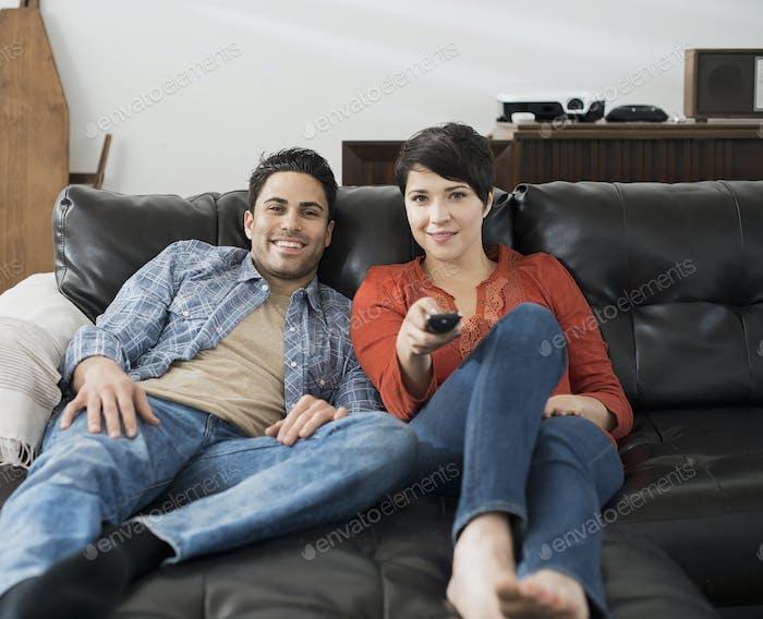 Ein Mann und eine Frau sitzen auf einem Sofa, Seite an Seite, eine mit der Fernbedienung für den Fernseher.