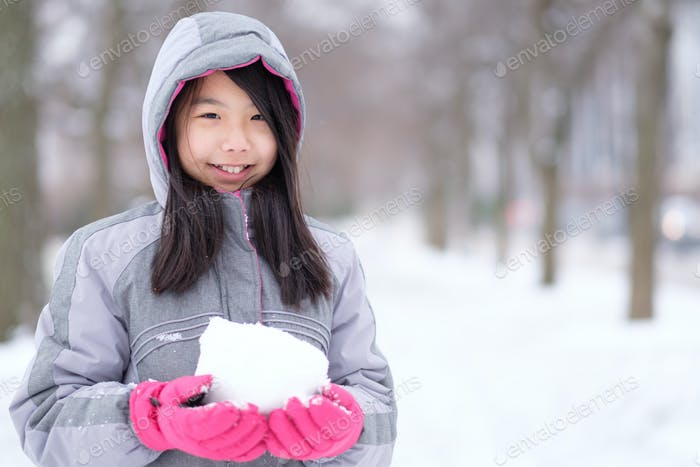 Portrait of Asian teen holding a snowball in hands