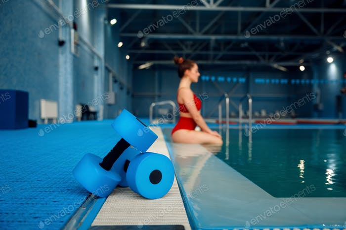 Female swimmer poses at poolside with dumbbells