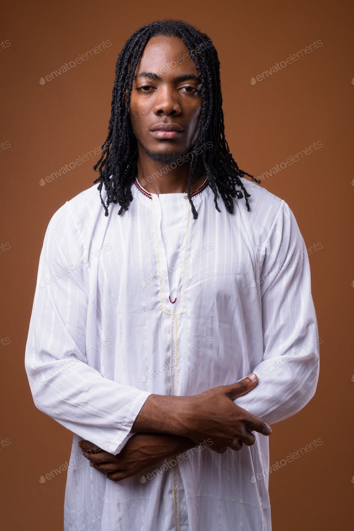 Young handsome African man wearing traditional clothes
