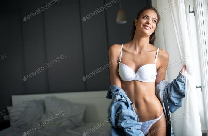 Portrait of beautiful sexy young woman with long hair and glamorous face in lingerie