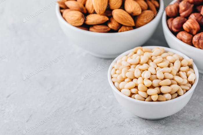 Pine nuts, almonds and hazelnuts in white bowls on grey background.