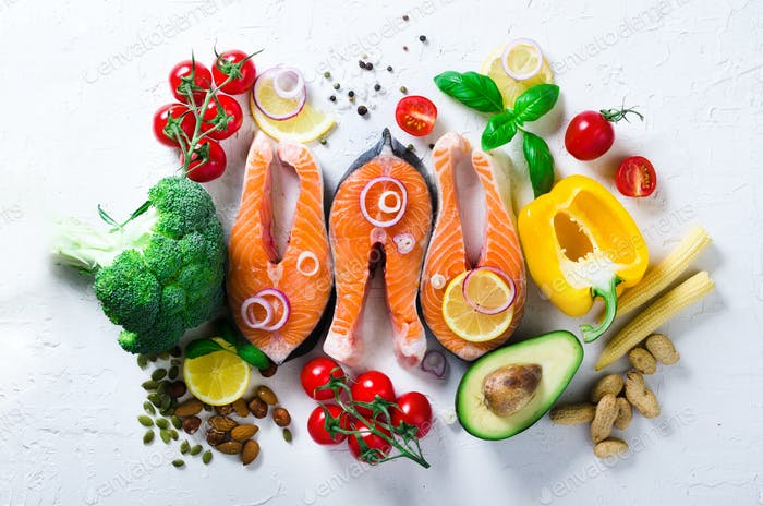 Uncooked salmon fish fillet with aromatic herbs, onion, avocado, broccoli, pepper bell, vegetables