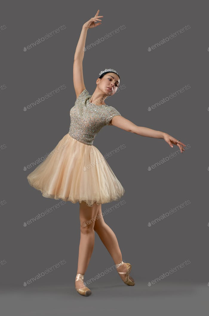 Ballerina in beige dress and ballet shoes dancing in studio