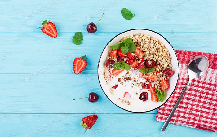 Healthy breakfast - granola, strawberries, cherry, honeysuckle berry, nuts and yogurt