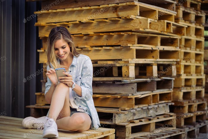 Charming girl sitting on a pallet using smart phone