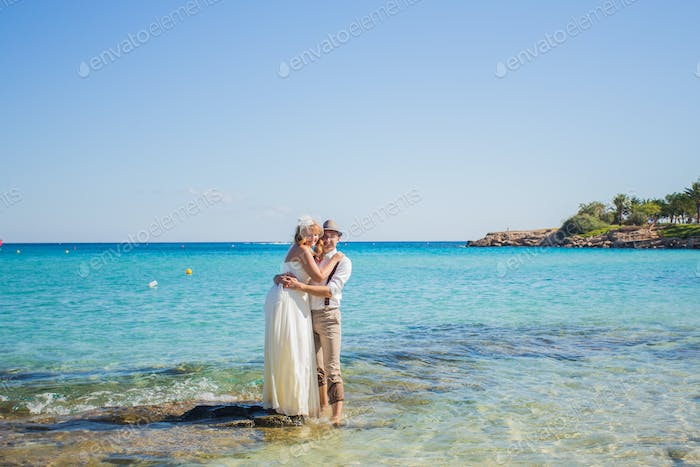 Bride and groom having fun at sandy tropical beach