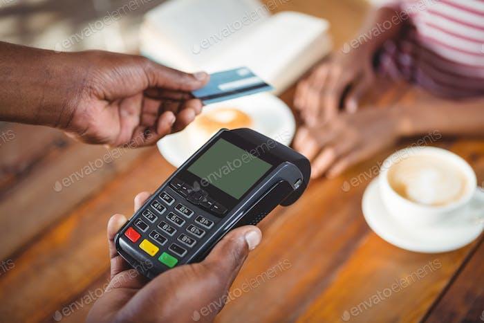Waiter holding credit card machine