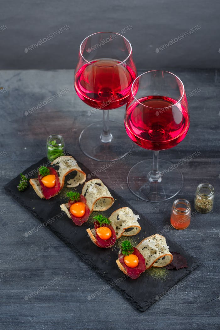 Appetizers - cured meat, crusty bread, yolk and cheese - on stone board with two glasses of wine
