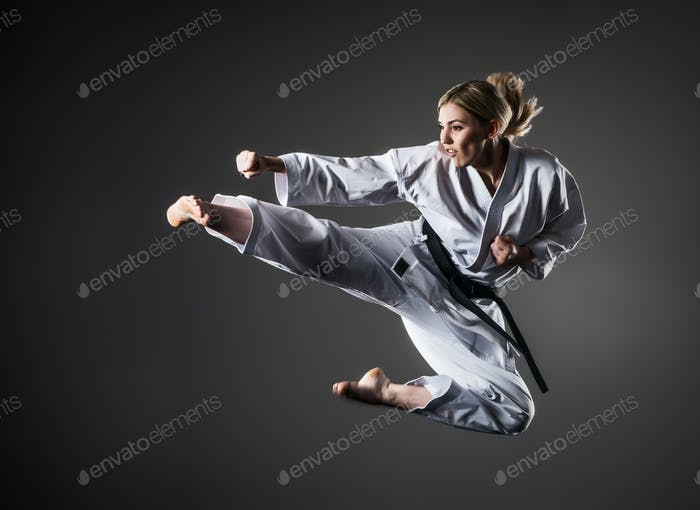 Composite image of karate girl jumping on dark background