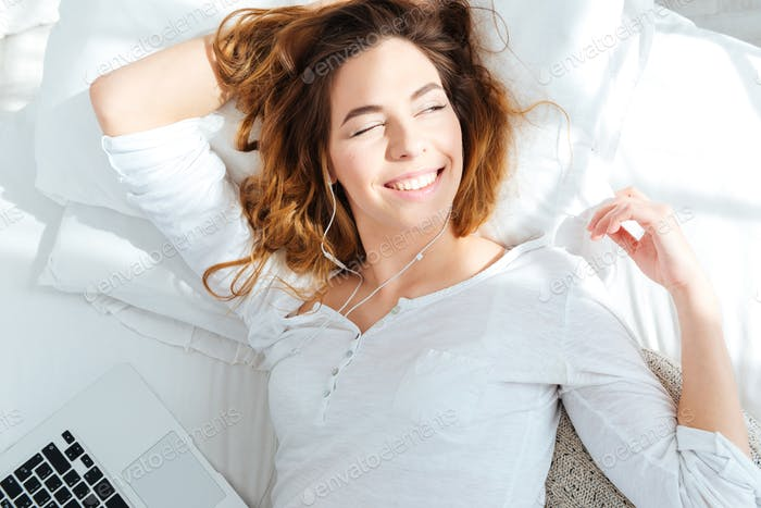 Happy woman lying on the bed and waking up