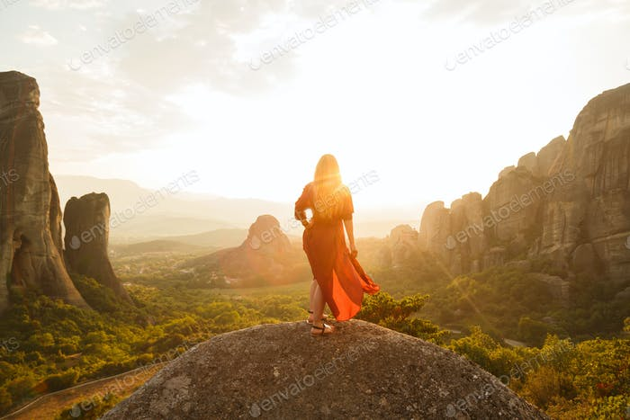 Thumbnail for Young woman in red dress looking at majestic sunset in Meteora valley, Greece
