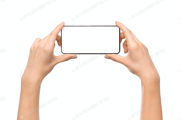 Young woman holding smartphone with blank screen in horizontal orientation