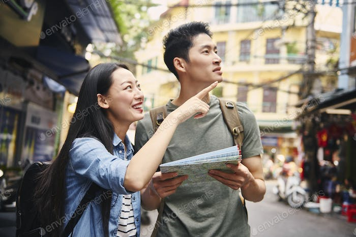 Vietnamese tourists with paper map