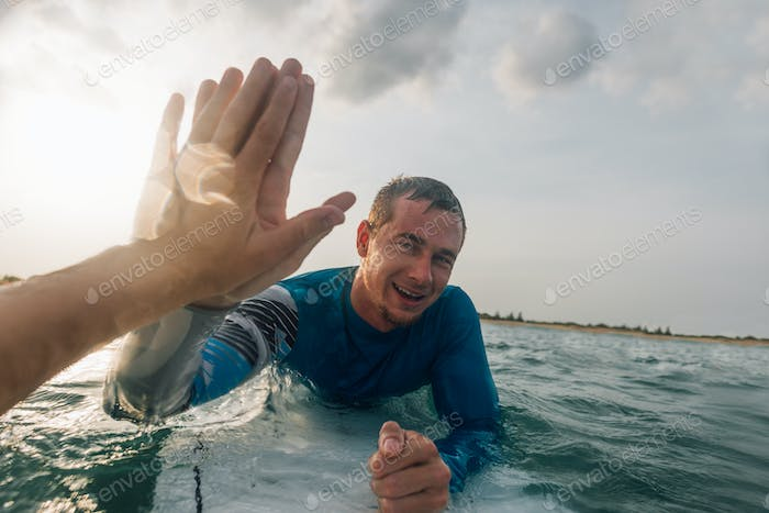 from first person, give five surfers on the water