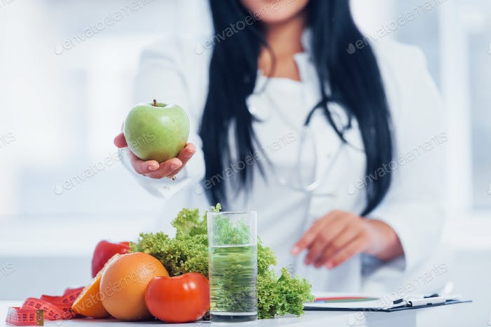 Female nutritionist in white coat holding apple in hand