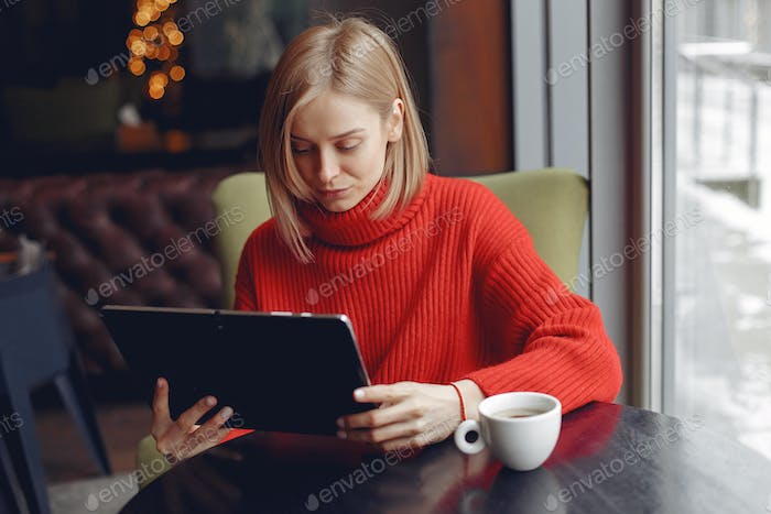 Businesswoman in a red sweater works