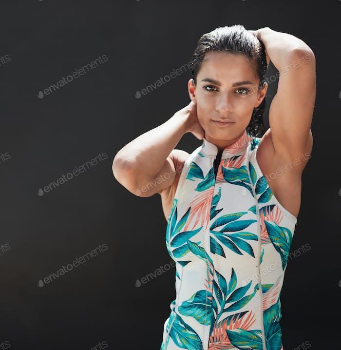 Beautiful young female model posing over black background