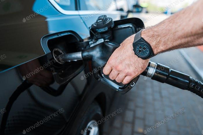 abgeschnittene Ansicht eines Mannes mit Kraftstoffpumpe und Tanken des Automobils an einer Tankstelle