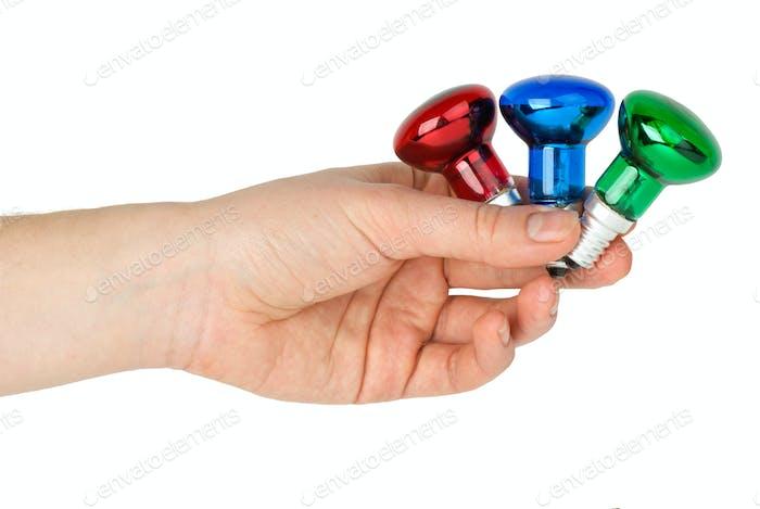 Hand halten winzige rote, blaue und grüne Flecken Wolfram Glühbirnen