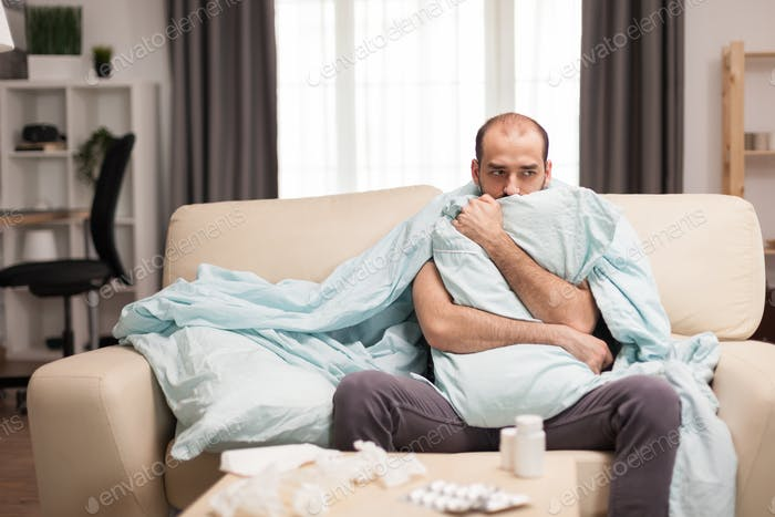 Sick man with chills wrapped in blacket