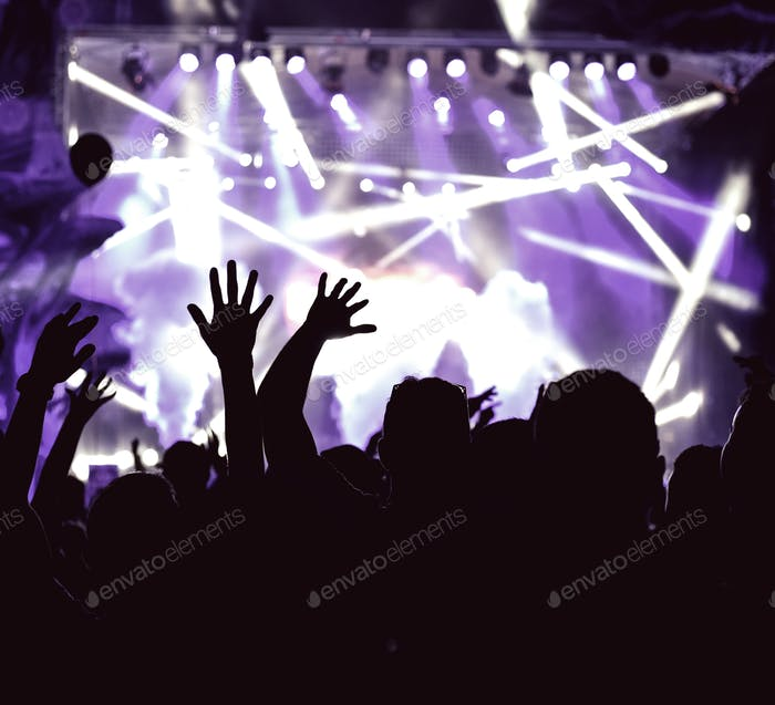 Crowd of audience with hands raised at a music festival. Lights streaming down from above the stage