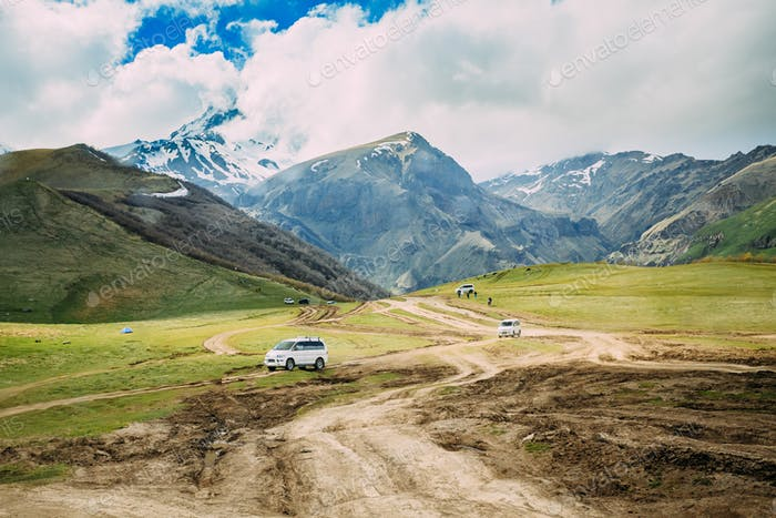 Tourist Cars SUV Go On Off Road With Views Of Mount Kazbek Near Village Of Gergeti In Georgia
