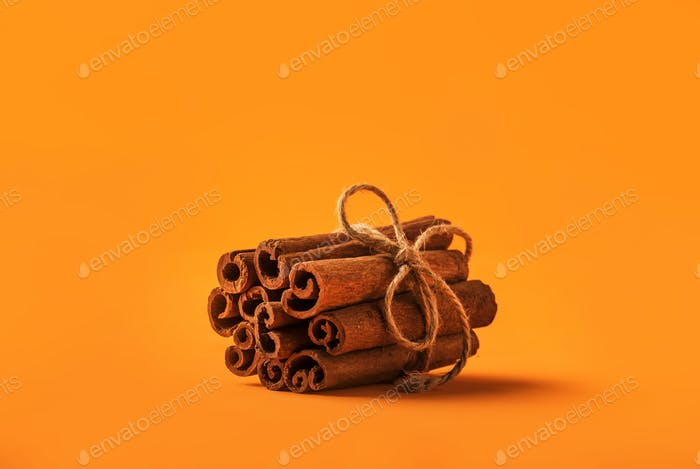 Cinnamon sticks tied with jute rope on orange background