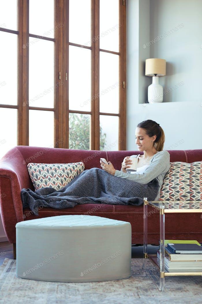 Hübsche junge Frau mit ihrem Handy, während Kaffee auf dem Sofa zu Hause trinken.