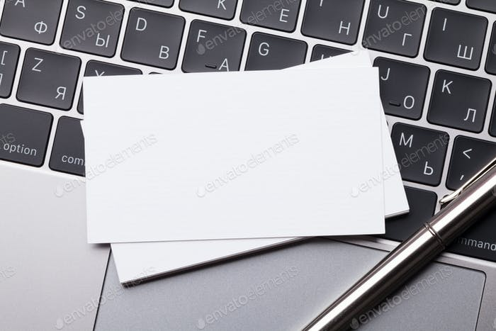 Blank business cards over laptop keyboard