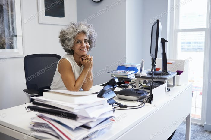 Middle aged businesswoman smiling to camera in her office