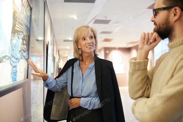Lächelnde Frau zeigt auf Malerei in Kunstgalerie