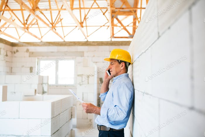 Senior architect with smartphone at the construction site.