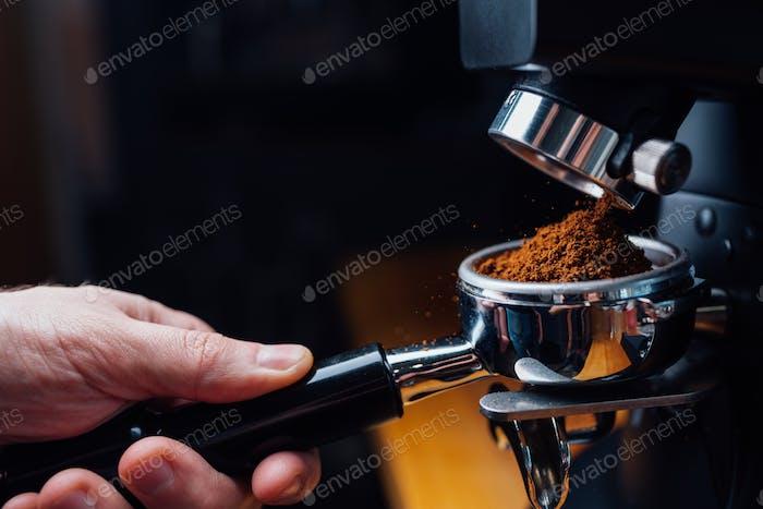 gemahlener Kaffee in einen Portafilter mit einer Mühle gießen
