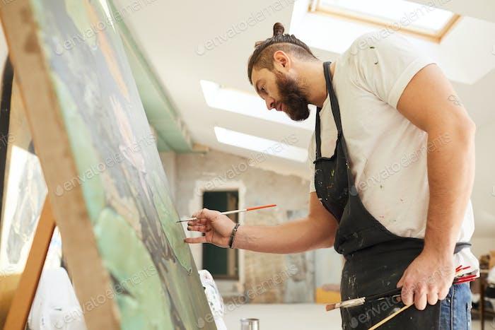 Bearded Artist Painting on Easel in Art Studio